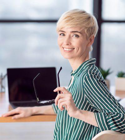 smiling-businesswoman-posing-holding-eyeglasses-si-H7WWSK5.jpg